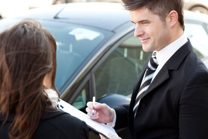 Confident businessman undersign a car contract outdoors